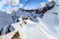 Sedie libere dell'ascensore della teleferica di una stazione sciistica vuota su un fondo nevoso di inverno del pendio e del cielo Immagini Stock