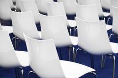 Sedie nella stanza di affari, file di conferenza dei sedili comodi di plastica bianchi nell'ufficio corporativo vuoto di riunione Fotografia Stock
