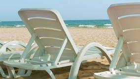 Sedie o letti di spiaggia bianchi vicino alla riva dell'oceano o del mare stock footage