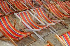 Sedie prendenti il sole di rilassamento sulla spiaggia Fotografia Stock