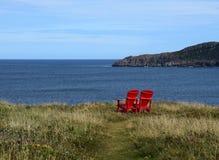 Sedie rosse di Adirondack sull'orlo di una scogliera che trascura l'oceano immagini stock libere da diritti