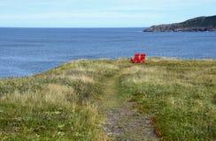 Sedie rosse di Adirondack sull'orlo di una scogliera che trascura l'oceano immagine stock libera da diritti