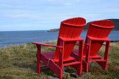 Sedie rosse di Adirondack sull'orlo di una scogliera che trascura l'oceano fotografia stock