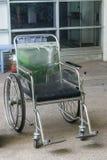 Sedie a rotelle ai disabili in una stanza con il pavimento di calcestruzzo fotografia stock
