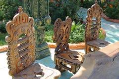 Sedie scolpite di legno in un giardino Fotografia Stock