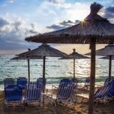 Sedie a sdraio di fila sulla spiaggia al tramonto Immagini Stock