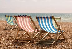 Sedie a sdraio a strisce rosse, blu, verdi e bianche classiche sul bea fotografia stock