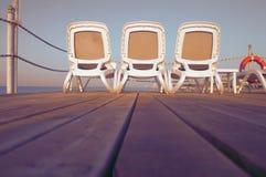 Sedie a sdraio su un pilastro che trascura il tramonto del mare Fotografia Stock