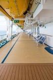 Sedie sulla piattaforma della nave da crociera sotto le lance di salvataggio Fotografia Stock Libera da Diritti