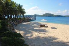 Sedie sulla spiaggia sabbiosa vicino al mare fotografia stock