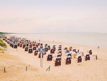 Sedie tipiche del canestro della spiaggia sulla spiaggia sabbiosa Mare blu basso, giorno soleggiato Fotografie Stock Libere da Diritti