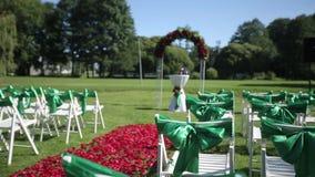 Sedie verdi di nozze in una cerimonia aperta con i fiori e gli ornamenti stock footage