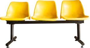 Sedie vuote gialle nell'ambito dei precedenti bianchi Immagine Stock