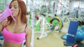 Sediento femenino juguetón después del entrenamiento activo, agua dulce de consumición almacen de metraje de vídeo