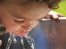 Sediento, niño que bebe de la fuente Fotos de archivo libres de regalías