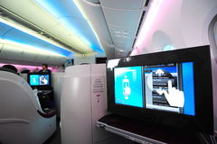 Sedile del Business class e sistema in volo Qatar Airways a bordo Boeing 787-8 Dreamliner di spettacolo a Singapore Airshow Fotografie Stock Libere da Diritti