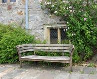 Sedile di banco in un giardino inglese di inizio dell'estate Fotografia Stock
