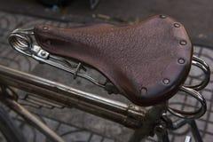 Sedile di bicicletta d'annata il marrone della sella sulla sella Fotografia Stock Libera da Diritti