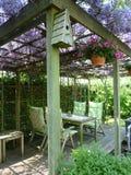 Sedile di giardino sotto le glicine Immagine Stock