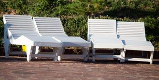 Sedili bianchi vicino allo stagno Fotografia Stock