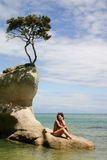 Sedili della donna su una roccia Abel Tasman Park, Nuova Zelanda Immagini Stock