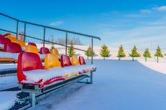 Sedili variopinti vuoti dello stadio di calcio di calcio nell'inverno coperto in neve - Sunny Winter Day con chiaro cielo blu in fotografie stock libere da diritti