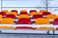 Sedili variopinti vuoti dello stadio di calcio di calcio nell'inverno coperto in neve - Sunny Winter Day con chiaro cielo blu in immagini stock libere da diritti