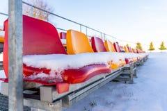 Sedili variopinti vuoti dello stadio di calcio di calcio nell'inverno coperto in neve - Sunny Winter Day con chiaro cielo blu in immagine stock libera da diritti
