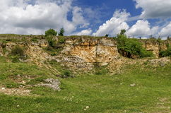 Sedimentary rock and meadow, Zavet town Royalty Free Stock Photo