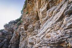 Cliffs in Budva. Sedimentary rocks along path from Oldt Town to Mogren Beach in Budva, Montenegro Stock Image