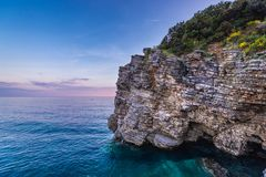 Rocks in Budva. Sedimentary rocks of cliff near small Mogren beach in Budva, Montenegro Stock Photography