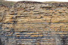 Sedimentary rocks in layers-stratum, strata. Geology. The strata of rocks seen in the side of a cliff on the coast. Various layers formed over thousands of stock photography