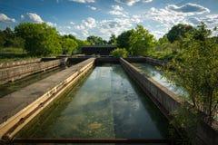 Sedimentation Tanks at Abandoned Sewage Treatment Plant. The slime covered sedimentation tanks, or pools, of an old, abandoned water sewage treatment facility Stock Photos