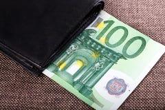 Sedlar av hundra euro som klibbar ut ur den svarta plånboken, stängde sig, Royaltyfri Bild