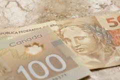 Sedlar av kanadensisk valuta: Dollar- och brasilianvaluta: R fotografering för bildbyråer