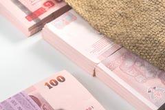 Sedlar av thailändsk baht 100 inom den åkerbruka säcken Royaltyfria Bilder