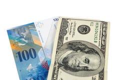 Sedlar av 100 US dollar och schweizisk franc Royaltyfria Bilder