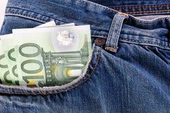 Sedlar hundra euro som klibbar ut ur den främre jeansen, stoppa i fickan Royaltyfri Fotografi
