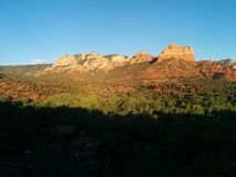 Sedona at sunset with vivid rock formations and deep shadows. With distant houses royalty free stock image