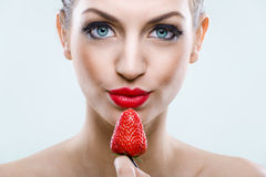 Seduction - Beautiful eyed woman holding a strawberry Royalty Free Stock Image