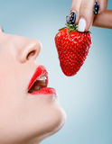 Seduction - Women's mouth eats strawberries Royalty Free Stock Photography