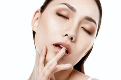 Seductive asian woman with closed eyes and finger on lip Royalty Free Stock Photo