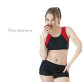 Seductive   athletic  girl   in tracksuit eating a red apple. Seductive   athletic  girl   in tracksuit eating a red apple on white background.Healthy lifestyle Stock Photography