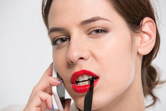 Seductive attactive young business woman talking on mobile phone. Closeup of seductive attactive young business woman with red lips talking on mobile phone over Royalty Free Stock Photo