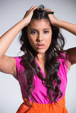 Seductive attractive brunette posing for camera ruffling hair Royalty Free Stock Photo