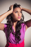 Seductive attractive brunette posing for camera ruffling her hair. On grey background Stock Image