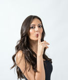 Seductive attractive tanned beauty woman with finger over her mouth hush gesture Stock Photos
