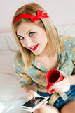 Seductive, beautiful pinup blond young woman blue eyes girl sitting in bed with mobile cell phone and red cup happy smiling Royalty Free Stock Photo