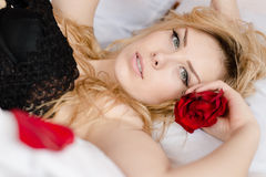 Seductive beautiful young blond woman having fun relaxing laying on bed with red rose & looking into the camera Royalty Free Stock Image