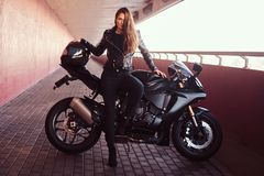A seductive biker girl leaning on her superbike on a sidewalk inside the bridge. A seductive biker girl wearing black leather jacket leaning on her superbike on royalty free stock photo